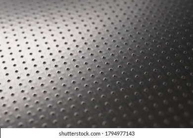 Dark industrial metallic background or wallpaper. Perforated aluminum surface with many holes. Perforation rows go into the distance and form a perspective. Macro