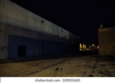 Dark industrial urban city alley at night with vintage warehouses