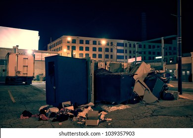 Dark industrial urban city street corner with trash and garbage dumpsters at night