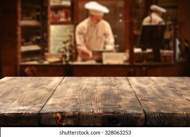 dark interior of restaurant with kitchen chef and deck top