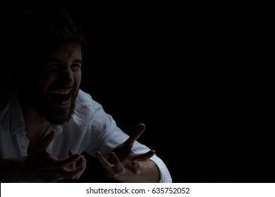 Dark interior with schizophrenic man with laugh attack