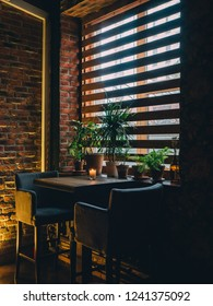 Dark interior with table and window of bar.