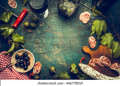 Dark italian food and antipasti background with wine,salami,olives and kitchen tools, top view, frame. Italian food background for menu or recipes .