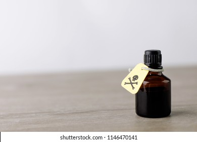 dark jar with poisonous solution, etiquette with a warning sign about the content of poisonous substances, on the table