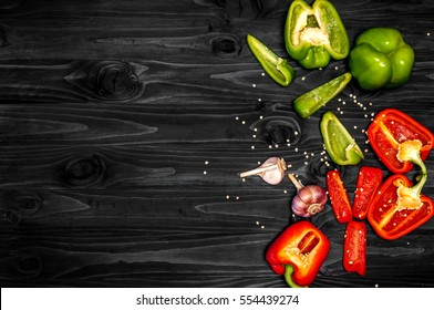 Dark kitchen table, red and green peppers, garlic, fresh organic vegetables, top view, space for text