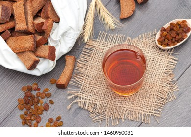 Dark kvass in glass with rye bread and raisins on wooden background