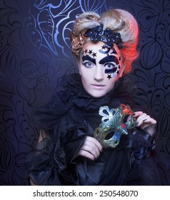 Dark Lady. Portrait of young woman in black posing with mask