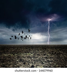 Dark landscape - bright lightning, flock of flying ravens, crows in dark moody sky, farm land