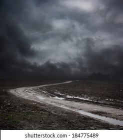 Dark Landscape with Dirty Road and Moody Sky. HDR Cloudscape.