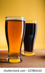 Dark and light beer in glass on wooden table