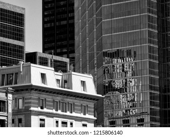 dark and light toned detail of skyscraper towers in monochrome with strong reflection