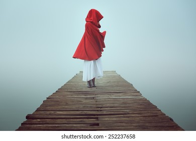 Dark little red riding hood in the mist . Dream and surreal colors
