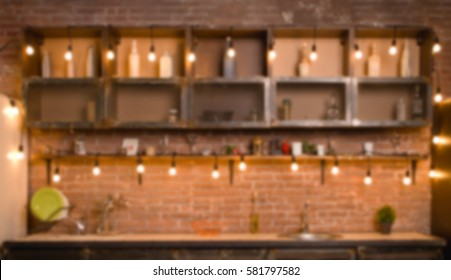 Dark loft kitchen with red brick. Kitchen table, headset, Cutlery, spoons, forks, oven, sink, fridge. Hang colourful retro filament lamp.