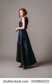 Dark long evening dress. Beautiful model wearing high heels, modern feminine look for an event. Women's fashion. Adorable ginger lady.
