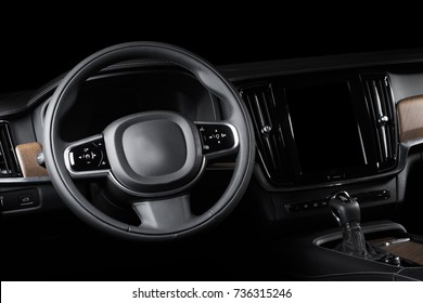 Dark luxury car Interior - steering wheel, shift lever and dashboard. Car interior luxury. Beige comfortable seats, steering wheel, dashboard, climate control, speedometer, display, light wood panels