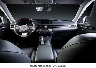 Dark luxury car Interior - steering wheel, shift lever and dashboard. Car inside. Beige comfortable seats, steering wheel, dashboard, climate control, speedometer, display.