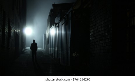 A dark male figure is silhouetted against a foggy urban alleyway