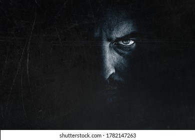Dark man portrait with scary evil eye. Spooky male face hiding in shadow, creepy frightening expression