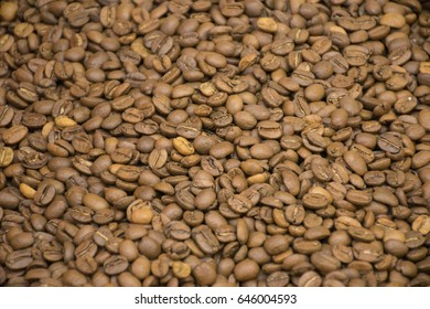Dark many roasted coffee beans texture background.