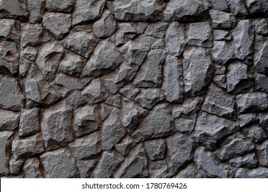 Dark masonry wall texture. Black stones and rocks of different shape, gray background
