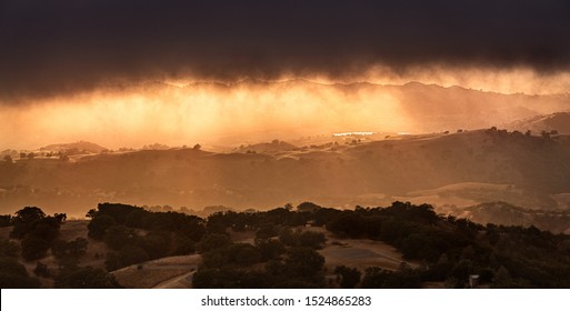 Dark and menacing storm clouds covering the sky at sunset; bright orange light illuminating hills and valleys in South San Francisco Bay Area; San Jose, California