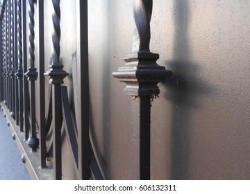 Dark metal fence with vertical figured bars