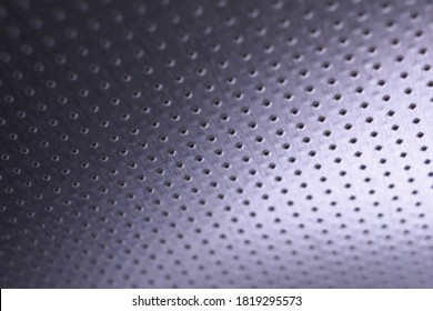 Dark metallic wallpaper. Tinted violet or purple background. Perforated aluminum surface with many holes, hanging from above like a ceiling. Perforation rows go into the distance and form perspective
