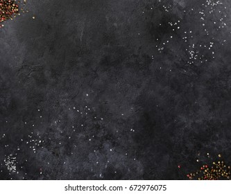 Dark mica background. Stone texture with sea salt and pepper. Spices laying on stone surface. Empty space for text. Can be used for food posters, design of menu and outdoor commercial