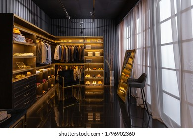 dark modern stylish male apartment interior with lighting, decorative walls, fireplace, dressing area and huge window - Shutterstock ID 1796902360