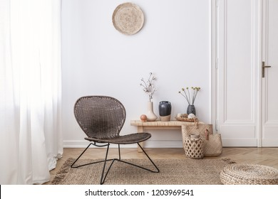 Dark, modern wicker chair in a white living room interior with a wooden bench and decorations made from natural materials