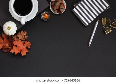 Dark and moody festive autumn desk top with nature items, coffee and office supplies. Black copy space.