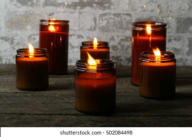 Dark, Moody Indoor Scene Of All Natural Soy Candles Lit And Glowing With Golden Light On Dark Solid Hardwood Table And Fairy Lights In Background