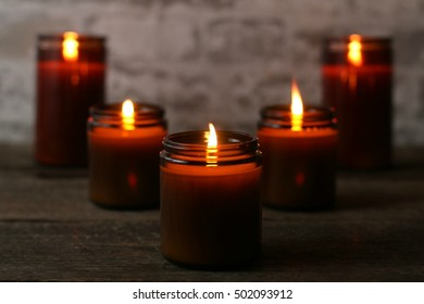 Dark, Moody Indoor Scene Of Five All Natural Soy Candles Lit And Glowing Golden On Old Hardwood Table With Stone Background During The Season Of Fall And Chilly Days