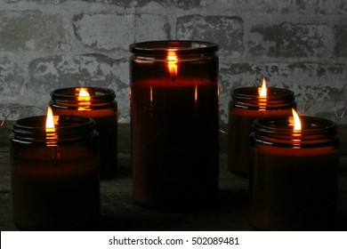 Dark, Moody Indoor Scene Of Lit All Natural Soy Candles Glowing Golden Colors On Old Hardwood Table With Stone Background