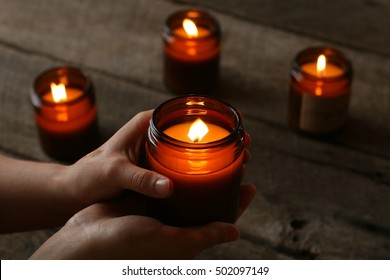 Dark, Moody Indoor Scene Of Two Hands Holding Warm Glowing Lit All Natural Soy Candle In Brown Glass Jar During The Season Of Fall And Chilly Days