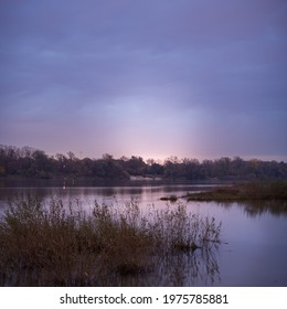 A dark, moody, mysterious shot with shallow depth of field of an evening river banks with a glowing purple sky in the distance that looks dangerous and like a bad place