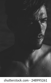 Dark moody portrait of an intense young man with a goatee frowning as he looks to the side, close up of his face and wet bare shoulders