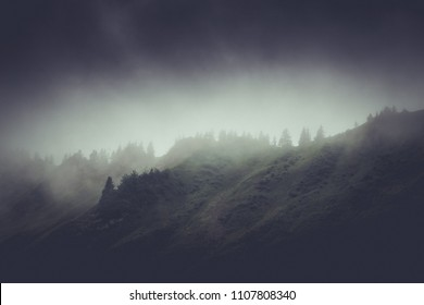 Dark moody rainy mountain landscape with low lying cloud or mist obscuring forested alpine mountain peaks in stormy weather with vignette