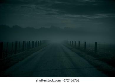 Dark moody road covered in mist