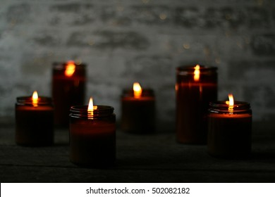 Dark, Moody Scene Of Golden Colored Glowing Lit All Natural Soy Candles In Brown Glass Jars During The Season Of Fall And Chilly Weather In The Mountains Of South West Virginia