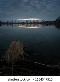 Dark moody sunset reflection in pond
