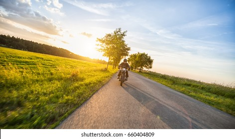 Dark motor biker riding high power motorbike in nature with beautiful sunset light. Travel and transportation. Freedom of motorbike riding
