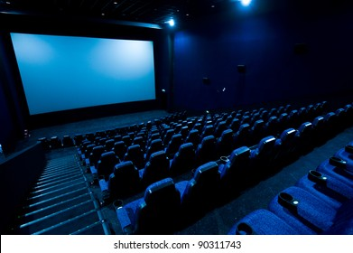 Dark movie theatre interior. screen, chairs
