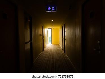 dark mysterious corridor in building, doors, perspective, in yellow- orange  tones.Thriller  or Horror Concept.