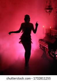 Dark mysterious silhouette in red smoke style retro woman. Girl dancing in short sexy vintage dress vogue 1930s, backdrop room piano burning candle old fashioned photo. Free space for an invitation