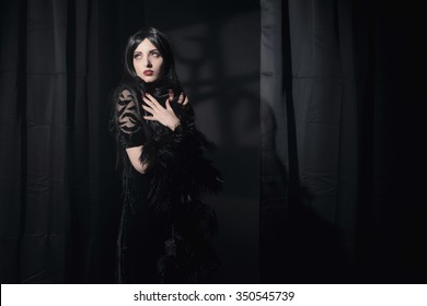 Dark mysterious witch fashion woman. Black curtains with window shadow on wall.