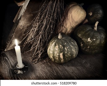 Dark mystic ritual with broom stick, candle and pumpkins by staircase.  Occult or esoteric concept with magic objects, Halloween background