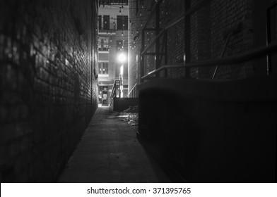 dark narrow alleyway at night, with street light illuminating the scene