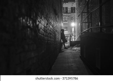 dark narrow alleyway with person posing by wall, with street light illuminating the scene.