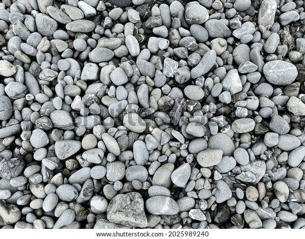a dark natural grey pebble rock stones as trail path or garden ground cover